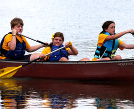 camp kids and counselors canoeing