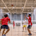 Photo of two students playing intramural Futsol. View from behind net