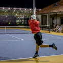 Photo of two students playing intramural tennis at night
