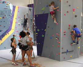 kids climbing rock wall with Tiger's Den