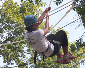woman swinging from ropes on challenge course