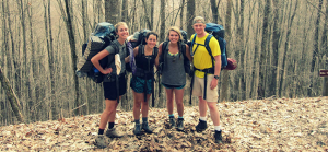 four people posing on hiking trail