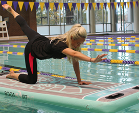 Photo of student in pool practicing BOGA. Left leg kicked out right arm out