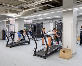 Photo of patrons in studio c on treadmill with trainer in room