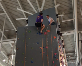 Photo of two workers on top of the climbing wall