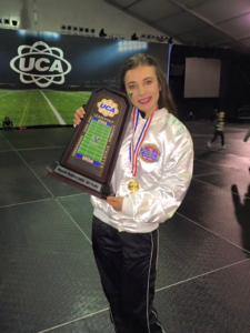 photo of cheerleader with trophy